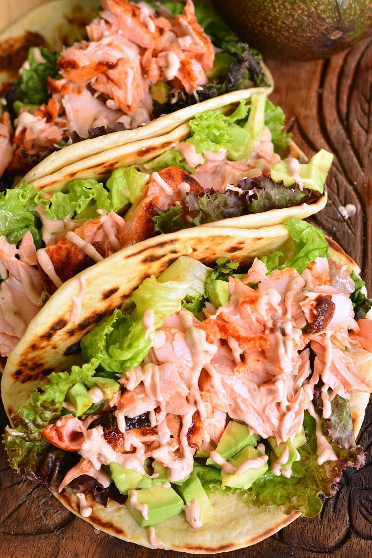 Easy Baked Salmon Tacos. Juicy, flaky salmon is rubbed with a mixture of spices and Chipotles in adobo sauce and baked. Tacos are simply assembled with some crunchy lettuce, avocados, salmon, and then topped with chipotle pepper cream sauce. #salmon #bakedsalmon #chipotlepeppers #tacos
