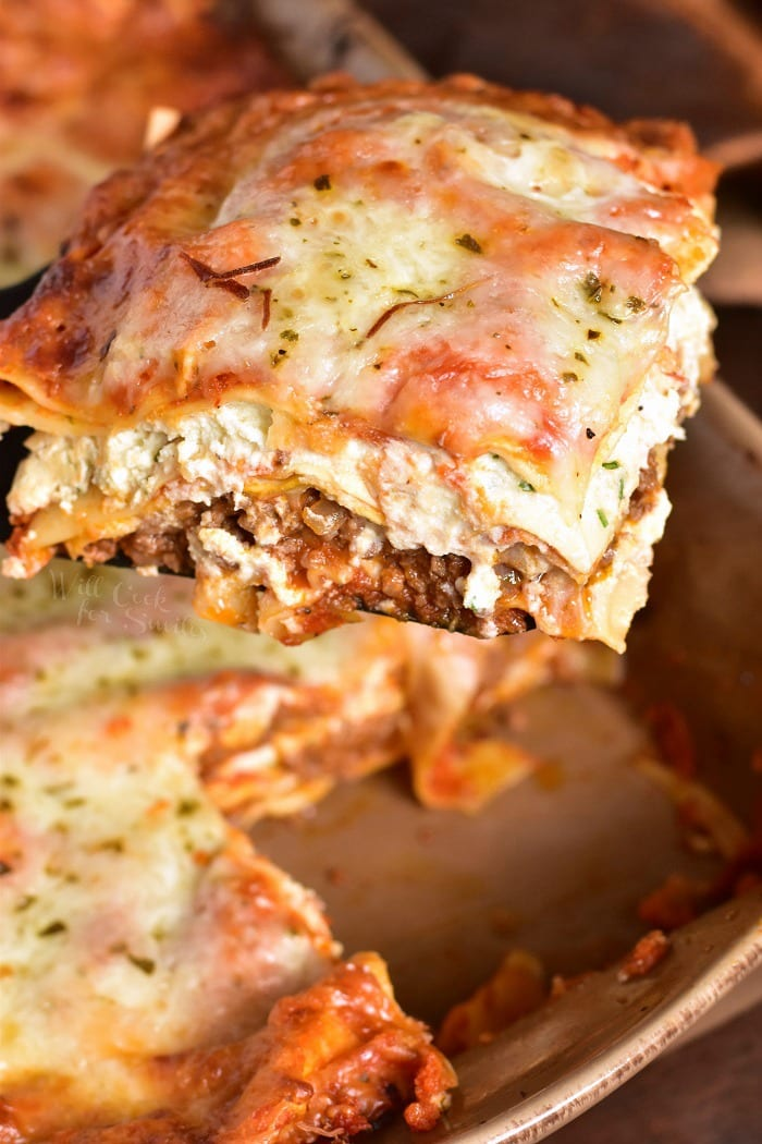 The BEST Lasagna in a baking pan lifting it out with a  spatula