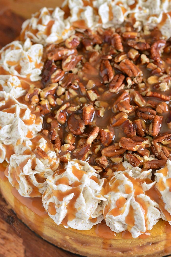 Pumpkin Cheesecake with Pecans and Caramel. Silky pumpkin cheesecake made with layers of caramel topping, pecan flavored crust, pecan buttercream frosting, and some more caramel and nuts on top. Beautiful fall dessert for your holiday dinner. #cheesecake #Pumpkincheesecake #pecan #buttercream #dessert #falldesserts #caramel