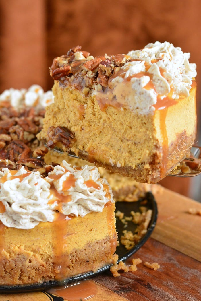 Caramel Pecan Pumpkin Cheesecake. Silky pumpkin cheesecake made with layers of caramel topping, pecan flavored crust, pecan buttercream frosting, and some more caramel and nuts on top. Beautiful fall dessert for your holiday dinner. #cheesecake #Pumpkincheesecake #pecan #buttercream #dessert #falldesserts #caramel