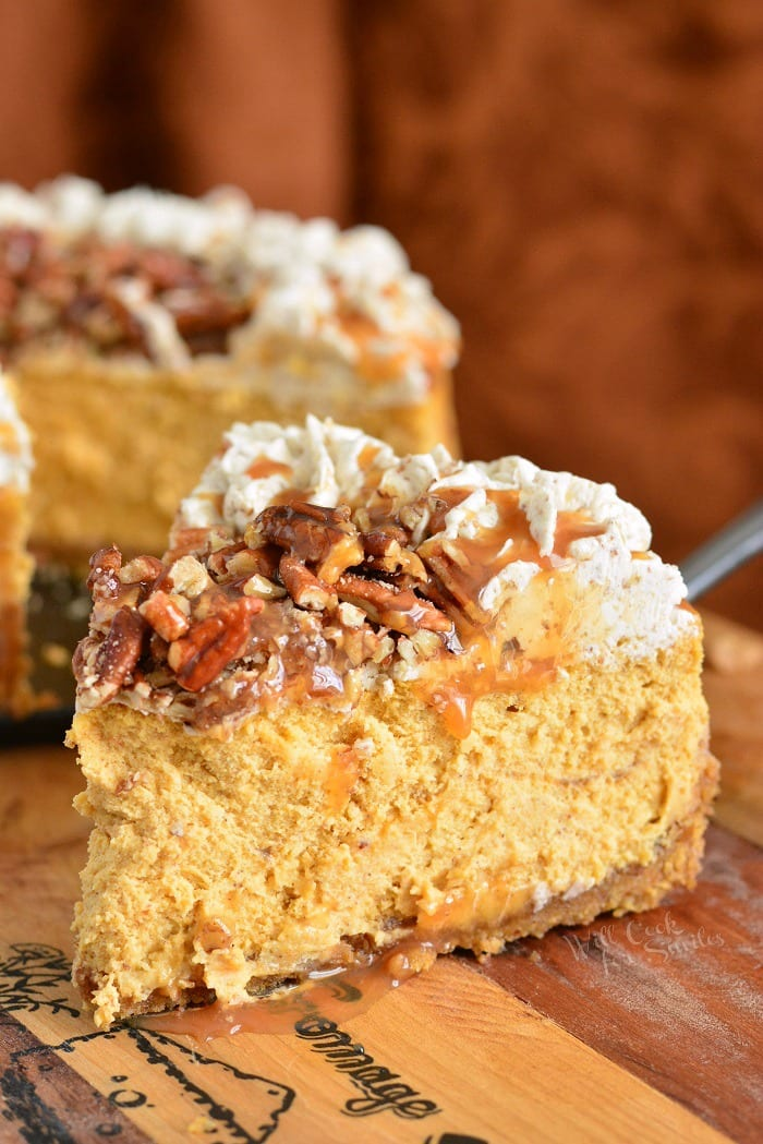 Pecan Caramel Pumpkin Cheesecake. Silky pumpkin cheesecake made with layers of caramel topping, pecan flavored crust, pecan buttercream frosting, and some more caramel and nuts on top. Beautiful fall dessert for your holiday dinner. #cheesecake #Pumpkincheesecake #pecan #buttercream #dessert #falldesserts #caramel
