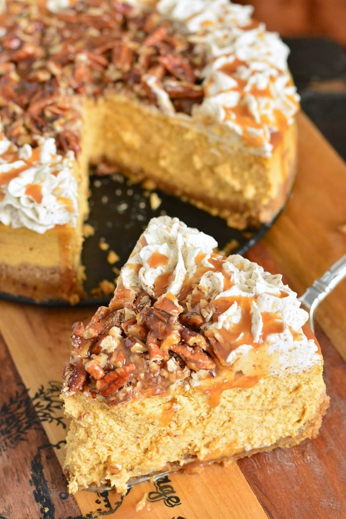 Pumpkin Cheesecake with Pecans and Caramel  slice on a wooden cutting board with the rest of the cheesecake in the background