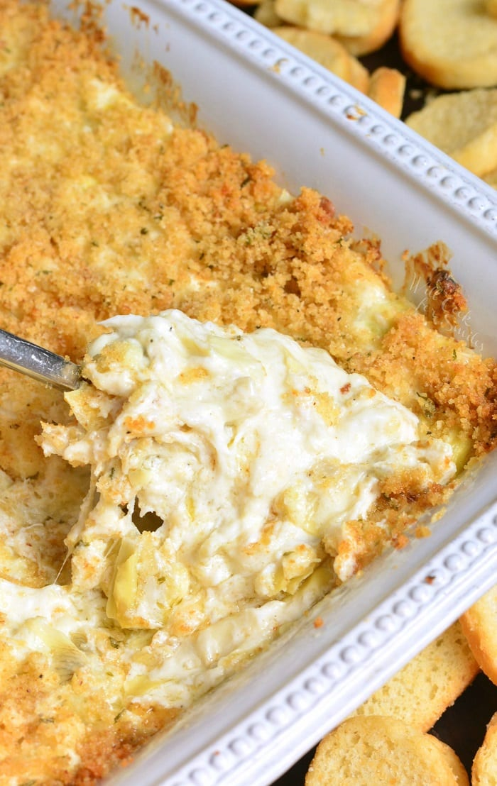 Artichoke Dip with Crab. This crowd pleasing dip is made with lump crab meat, artichoke hearts, and extra cheese. Buttery crumble on top is a perfect texture and flavor addition. #dip #cheesy #crabdip #artichokedip #hotdip #appetizer