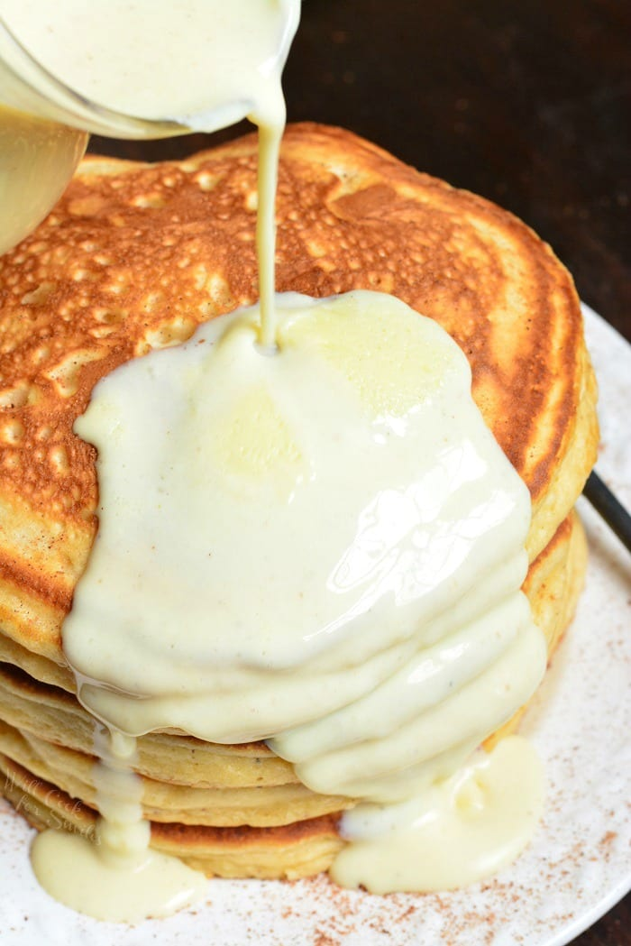pouring Eggnog sauce over Pancakes that are on a plate