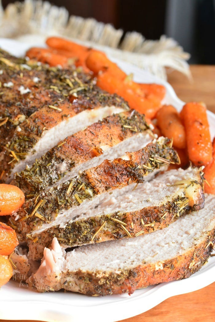 Garlic Pork Loin. This juicy and tender pork loin is baked on a bed of veggies for extra flavor and moisture, stuffed with garlic cloves, and rubbed with an herb mixture. #pork #maindish #porkloin #dinner