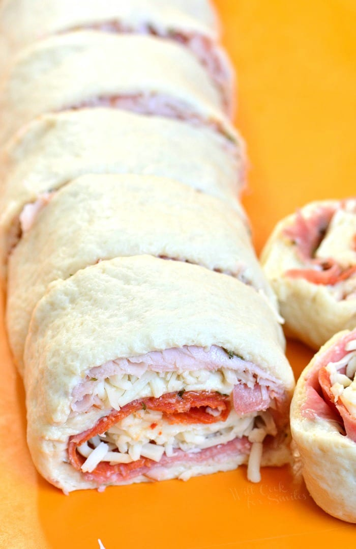 Italian Sub Pinwheels. Picture of step: roll up the dough and the filling started with covered edge and sealing the uncovered edge. Cut across the roll with serrated knife into pinwheels that are about 1 inch thick.