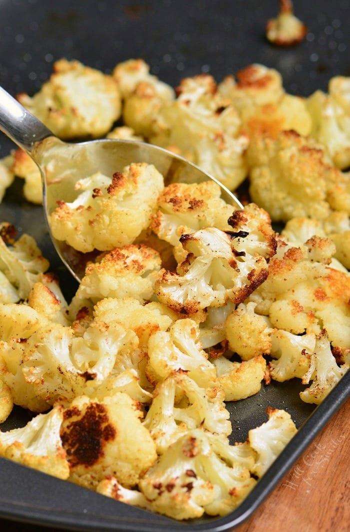 Roasted cauliflower on a baking sheet with a metal serving spoon