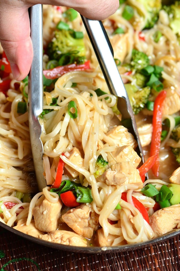 Sesame Chicken with Noodles in a pan lifting some out with tongs