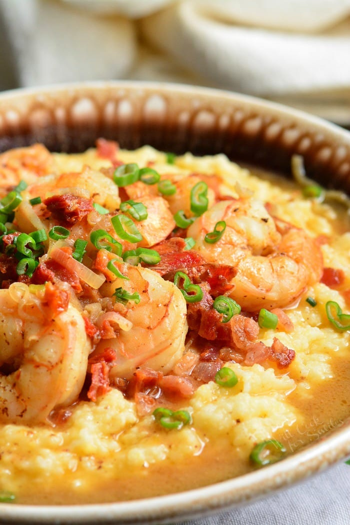 Shrimp and Grits is a wonderful southern classic that consists of buttery, cheesy grits topped with juicy shrimp that's been cooked with bacon and sub dried tomatoes. #shrimp #dinner #easydinner #grits