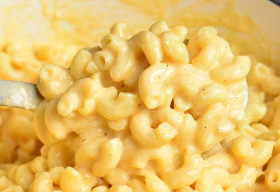 Easy Mac and Cheese Recipe in a pot being scooped out with a serving spoon