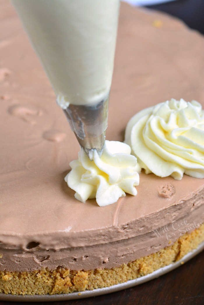 piping frosting onto cheesecake