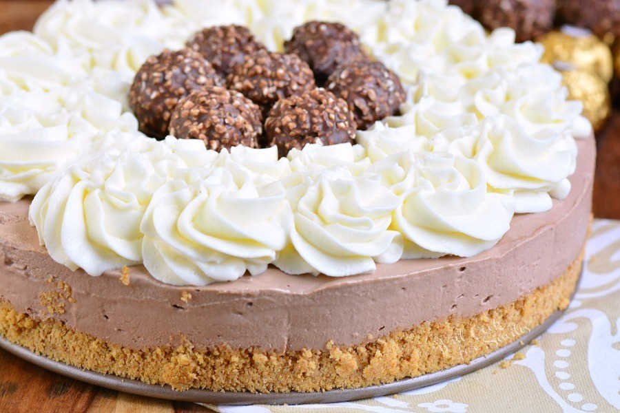 Nutella No Bake Cheesecake. Silky smooth No Bake Cheesecake made with a layer of buttery graham cracker crust, silky Nutella cheesecake, and whipped cream cheese frosting on top. #cheesecake #nobake #nutella #ferrerrorocher #frosting #dessert