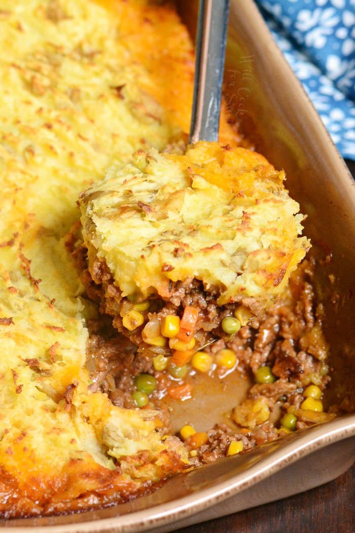 Shepherd's Pie in a casserole dish with a scoop being spooned out