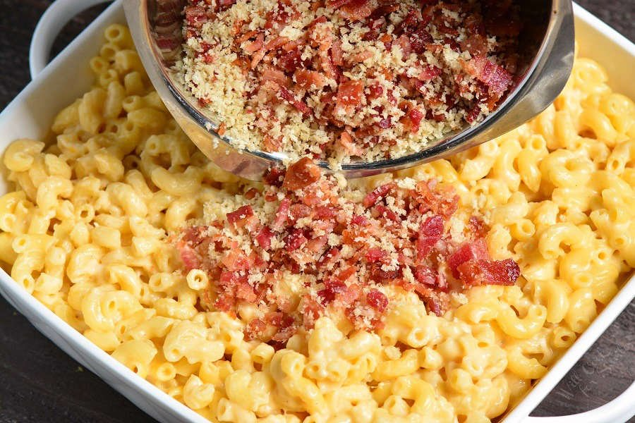 Baked Mac and Cheese in a casserole dish pourung bread crumbs with Bacon over the top.
