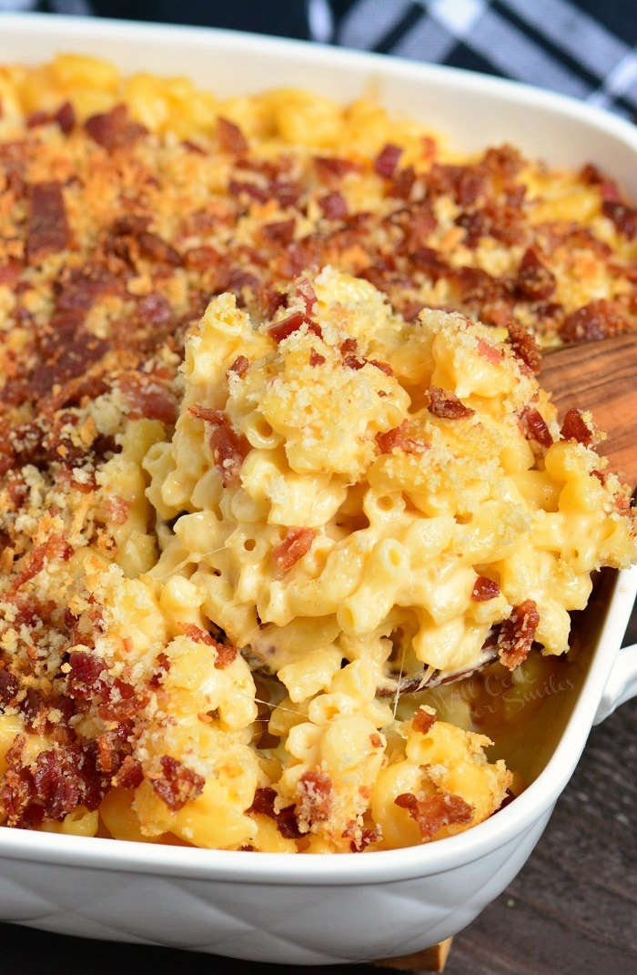 Baked Mac and Cheese in a casserole dish with a wooden spoon