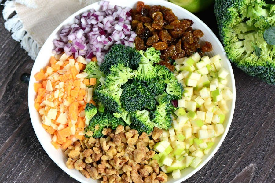 ingredients for broccoli salad in a serving bowl on a wooden cutting board