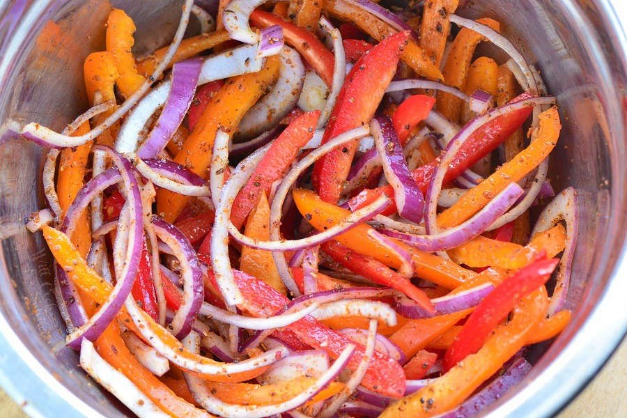 peppers and onions in a metal mixing bowl with spices