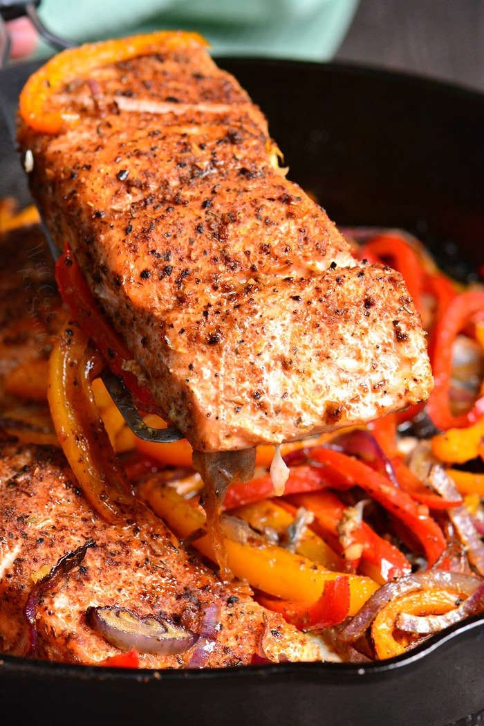 lifting cajun baked salmon out of cast iron pan with a spatula