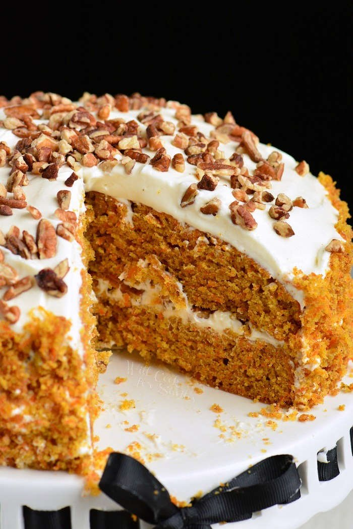 Easy Carrot Cake recipe. Moist, soft, and flavorful Carrot Cake is packed with freshly grated carrots, nuts, and spices and frosted with smooth cream cheese frosting. #cake #carrotcake #frosting #dessert #creamcheesefrosting