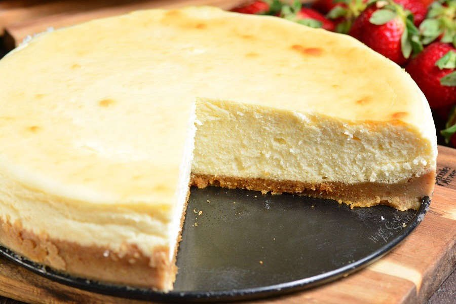 New York Cheesecake with a slice taken out on a wood cutting board