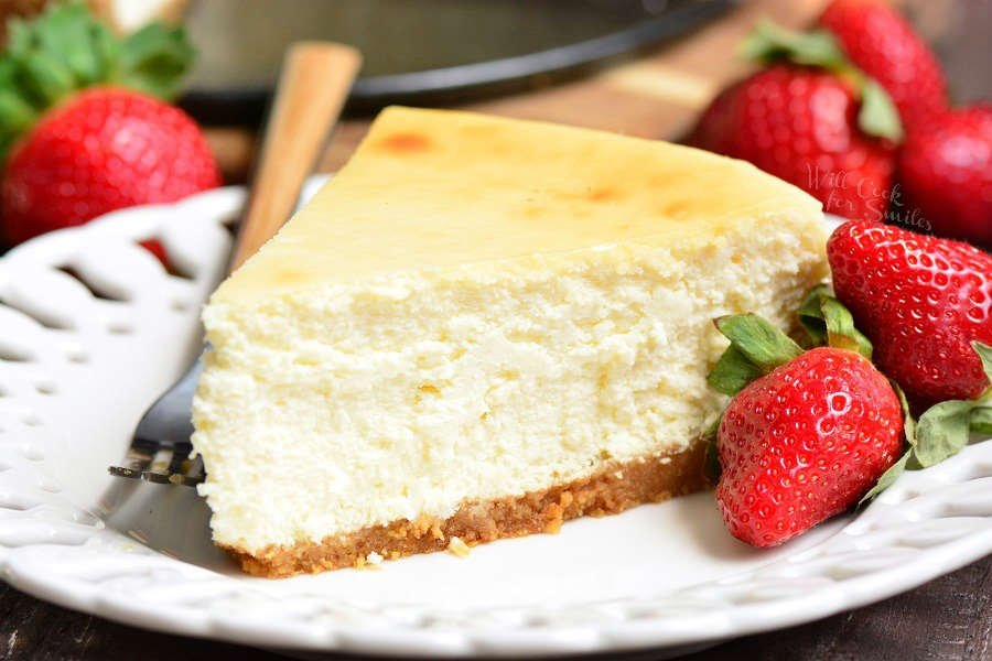 New York Cheesecake on a plate with strawberries and a fork