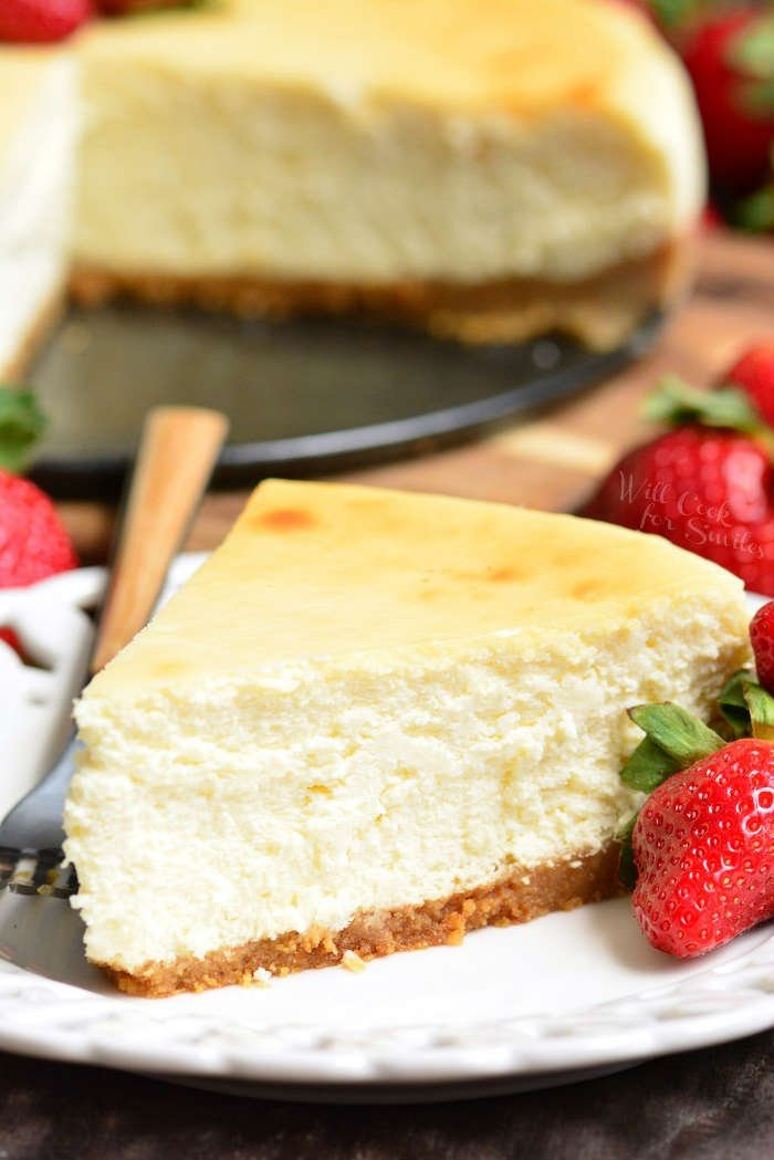 New York Cheesecake slice on a plate with a strawberry and fork