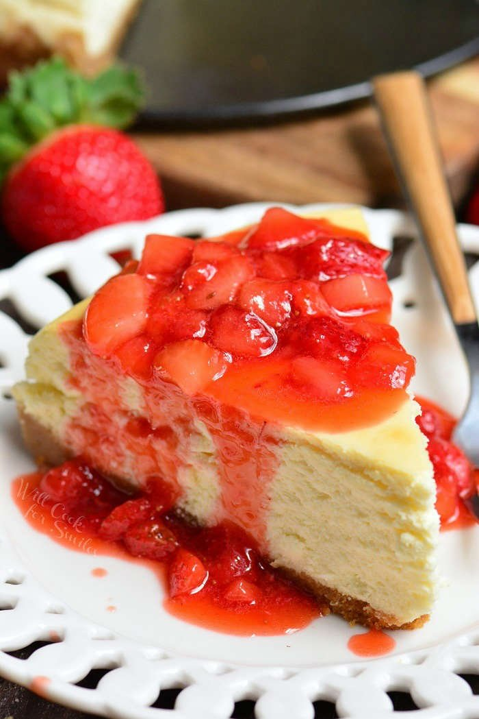 Piece of New York Cheesecake with strawberry sauce over the top in a plate