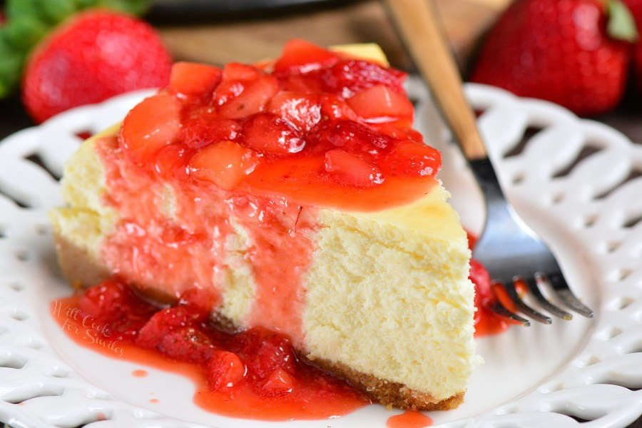 New York Cheesecake Recipe with strawberry sauce over top in a plate with a fork