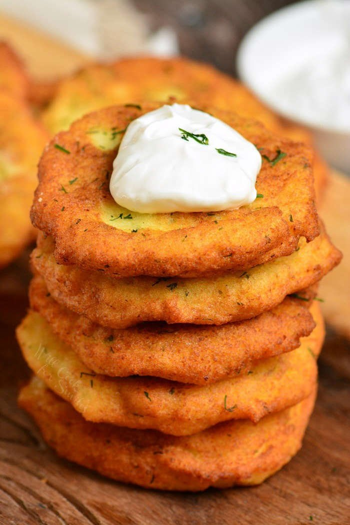 Classic potato pancakes stacked on a cutting board with sour cream on top