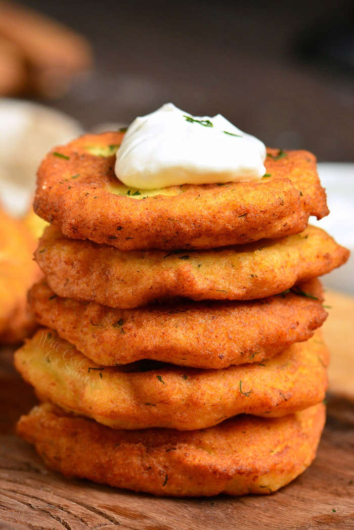 Classic potato pancakes stacked with sour cream on top sitting on cutting board
