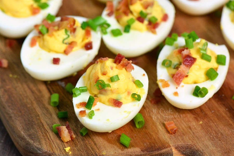 Classic Deviled Eggs with bacon and chives on top sitting on wood cutting board