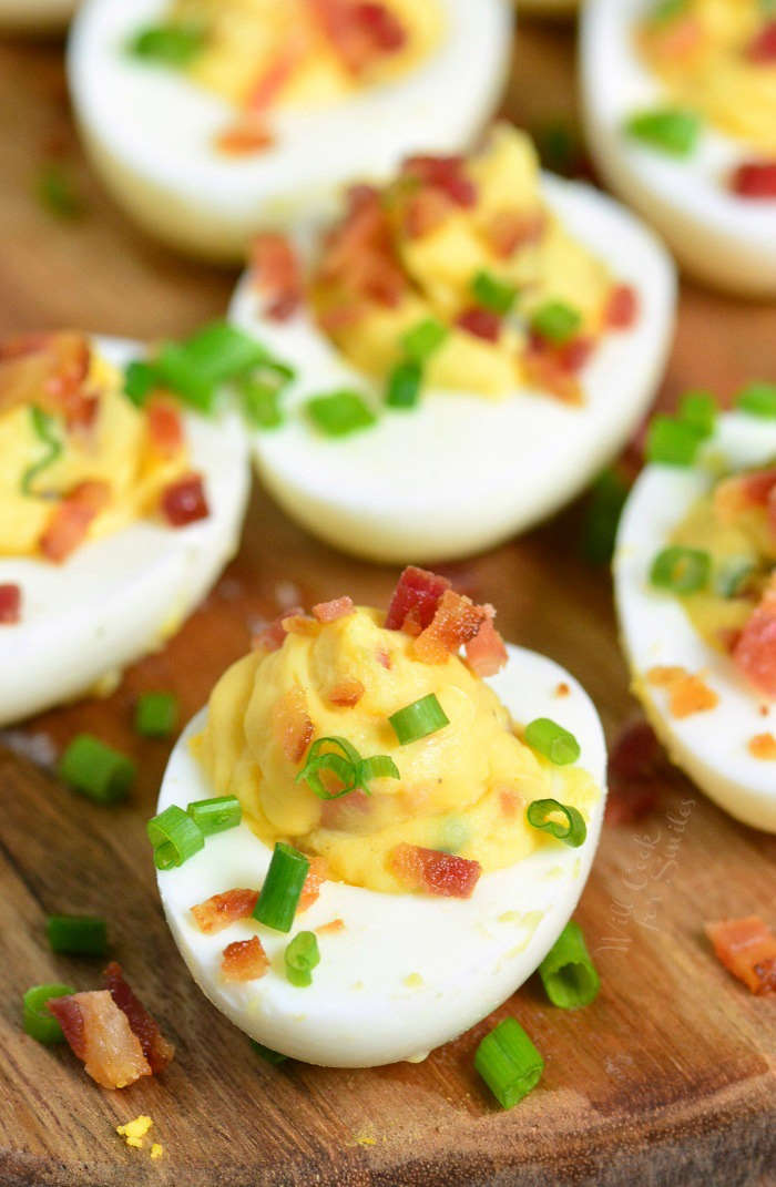 Bacon Deviled Eggs is a classic recipe taken to a whole new level. Hard boiled eggs are filled with a mixture of egg yolks, mayo, and mustard, bacon and chives.