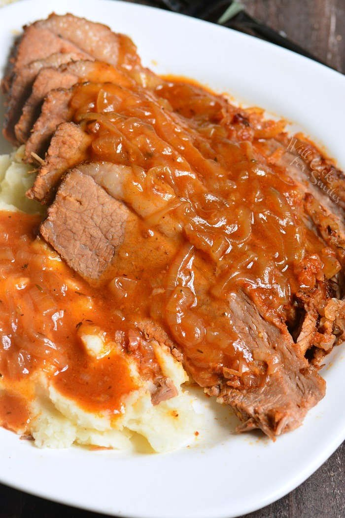 cooked beef brisket on a serving platter with mashed potatoes