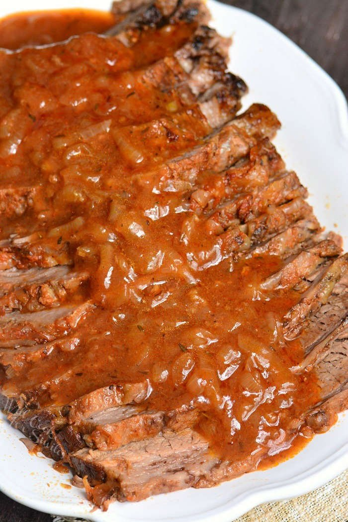 French Onion Beef Brisket sliced with French Onion gravy on a white serving platter