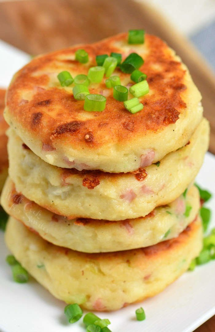 mashed potato cakes stacked on a white plate