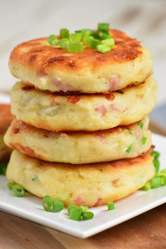 Ham and Cheese Mashed Potato Cakes stacked up on a white plate