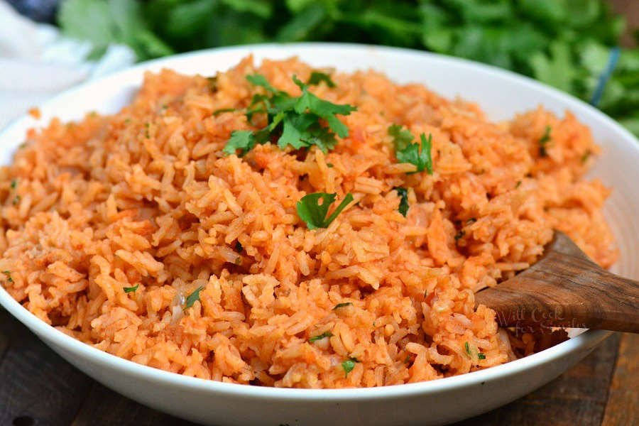 Spanish Rice in a serving bowl with a wooden spoon