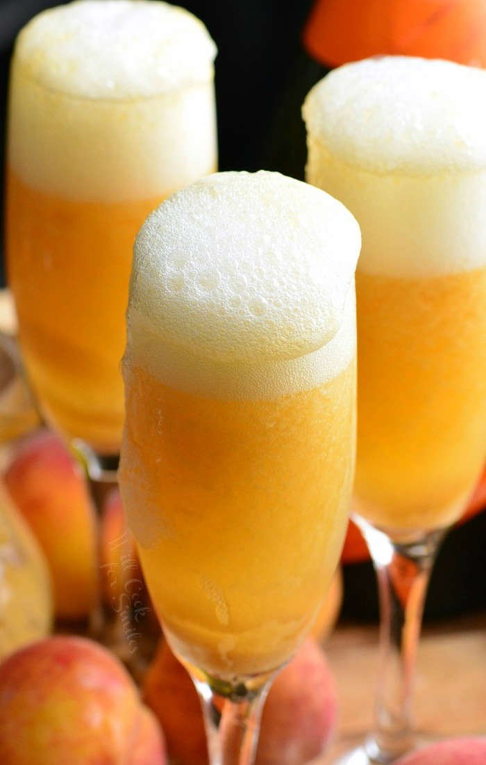 three Peach Bellini's in a champagne glass on a wood table with peaches