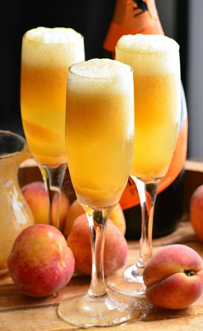 Peach Bellini in three champagne flutes on a wood table with peaches