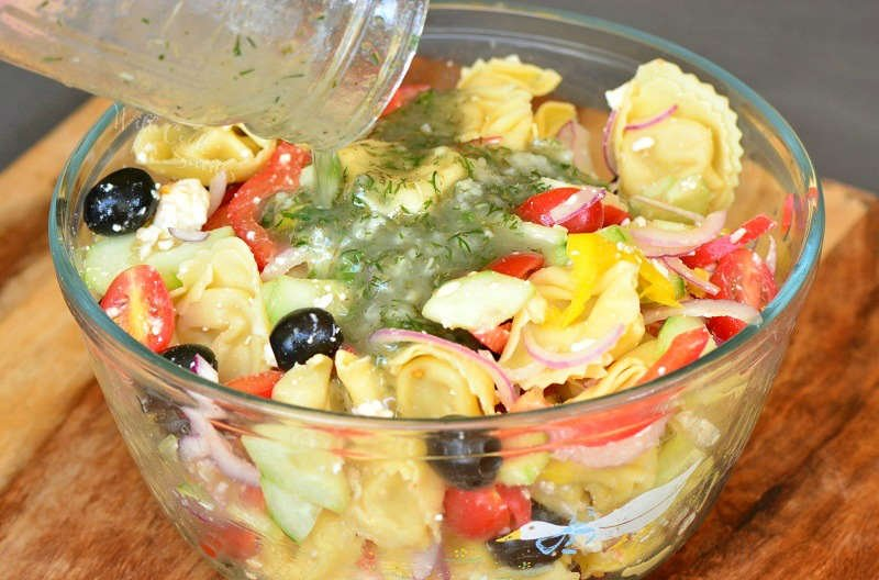 Add homemade Greek Dressing to the pasta salad that is in a glass bowl on a wood cutting board