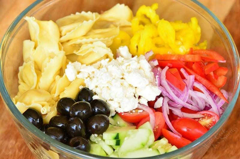 Ingredients in Greek Tortellini Salad in a glass bowl