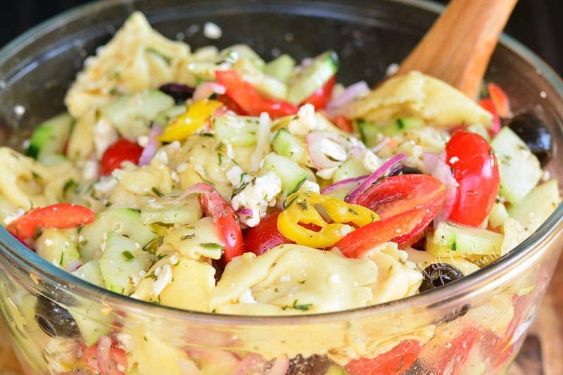 Greet Tortellini Salad in a glass bowl with a wooden spoon