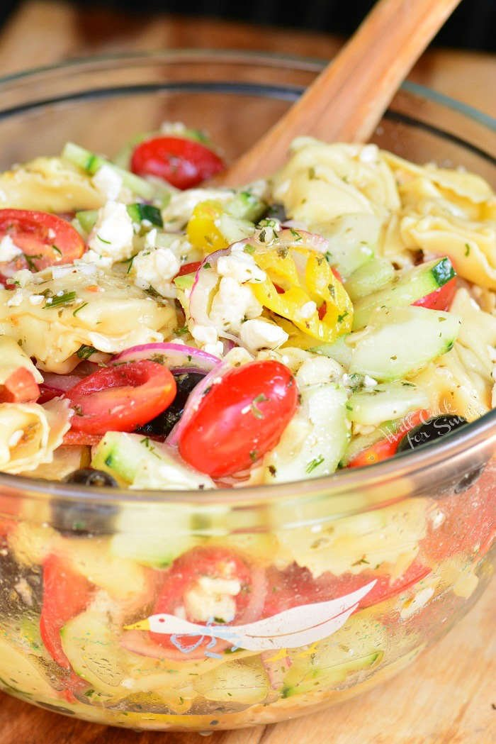 Greek Tortellini Pasta Salad in a glass bowl with a wooden spoon