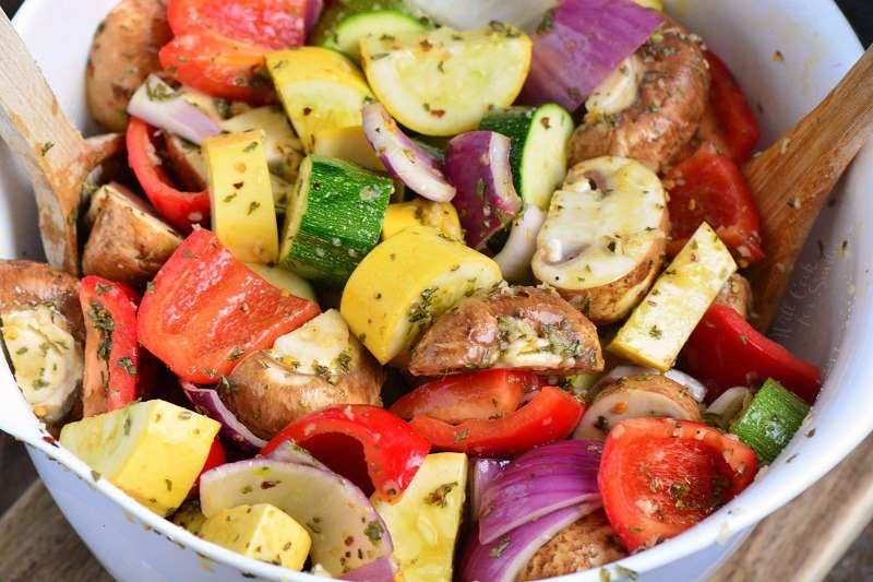 Marinade vegetables before grilling in a bowl with a wooden spoon