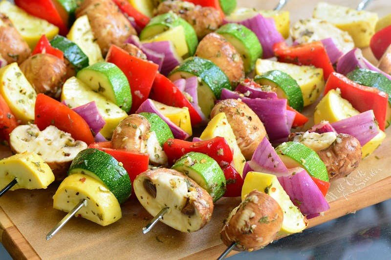 Grill vegetables on skewers on parchment paper on a wood cutting board