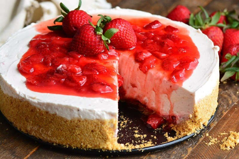 Strawberry No Bake Cheesecake with a slice missing on a wood table with strawberries