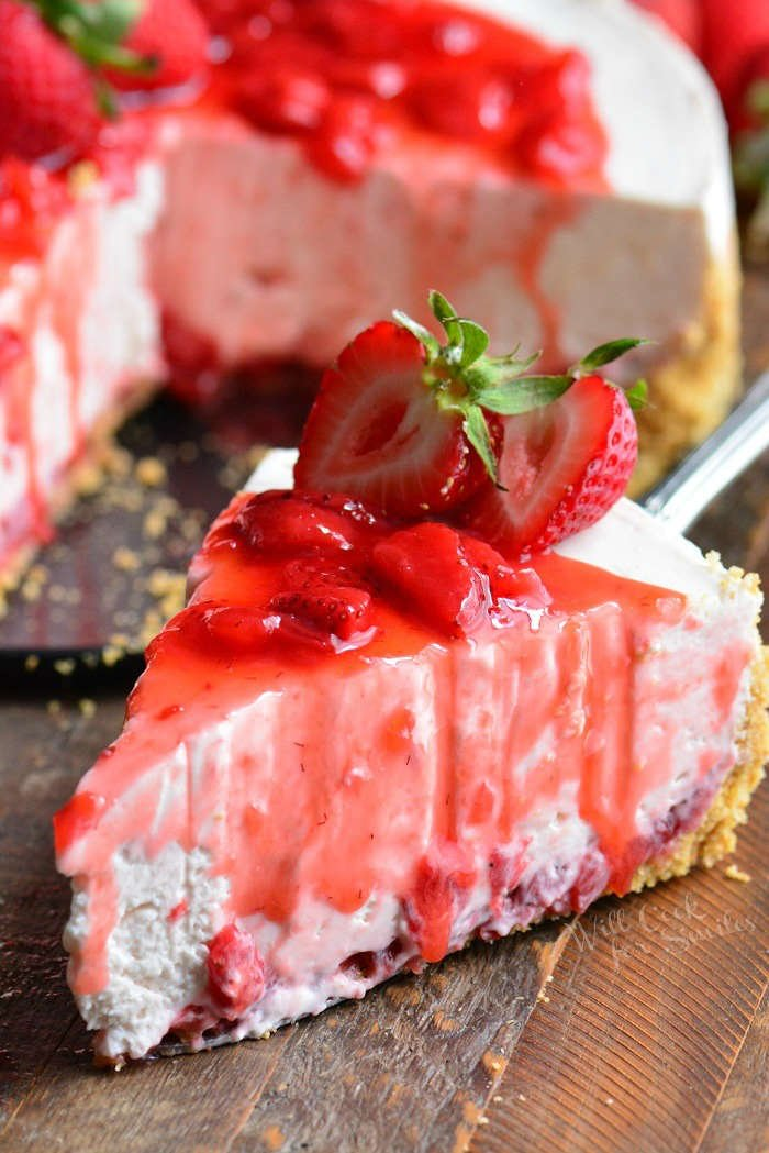 Strawberry No Bake Cheesecake slice on a wood cutting board