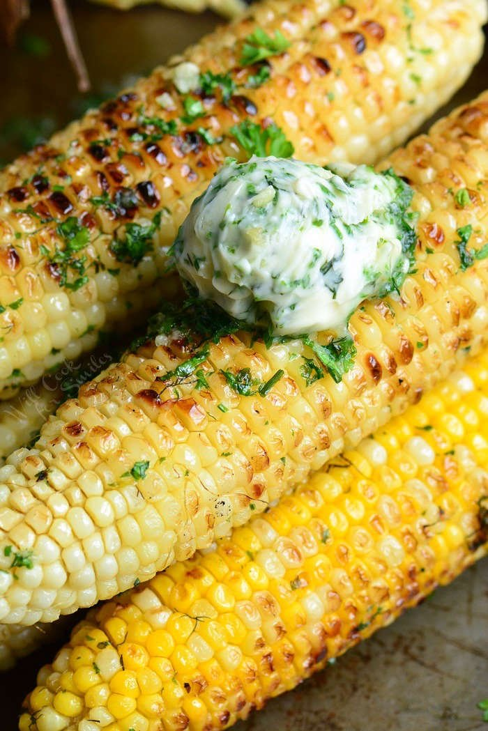 corn on the cob with garlic herb butter on a baking sheet