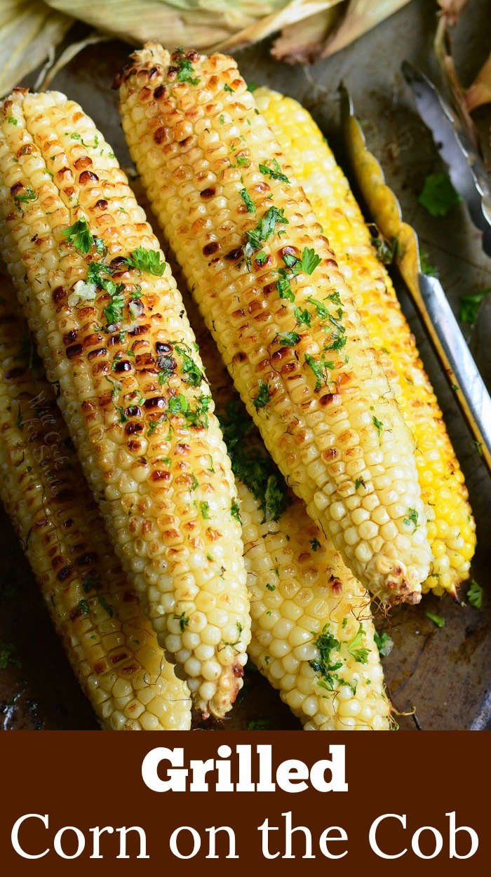 grilled corn with herb butter on a wood cutting board with metal tongs