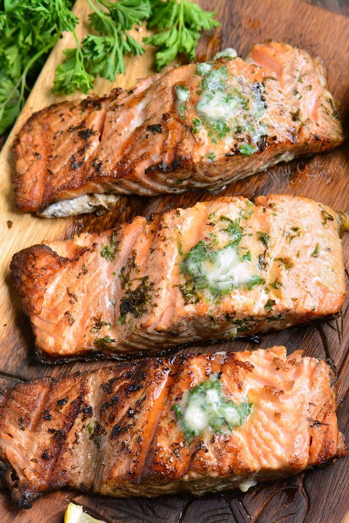 grilled salmon with herb butter on a cutting board